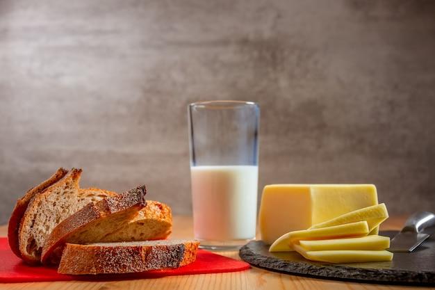 木製のテーブルの上の有機食品。焼きたてのパン、チーズ、ミルクのスライス