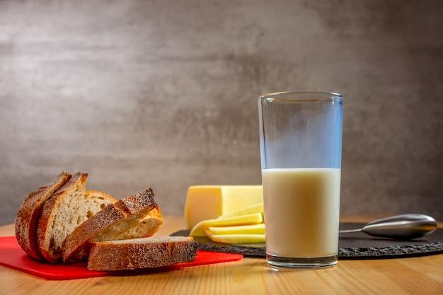木製のテーブルの上の有機食品。フレッシュチーズ、パン、ミルクのスライス