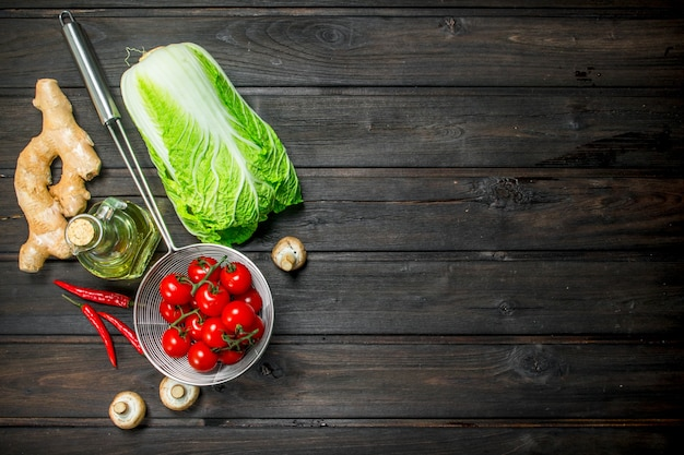 Organic food. ripe tomatoes with green vegetables on rustic table.