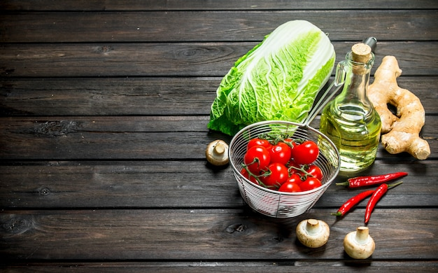 Organic food. ripe tomatoes with green vegetables. on a wooden surface.