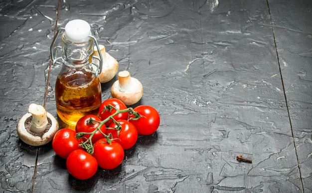 Organic food. ripe tomatoes with mushrooms and olive oil. on a black rustic table.