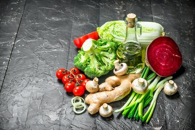 自然食品。オリーブオイルのボトルで熟した野菜。素朴な黒に。