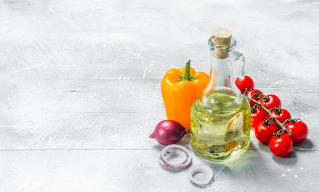 유기농 식품. 올리브 오일과 잘 익은 야채. 소박한 배경.