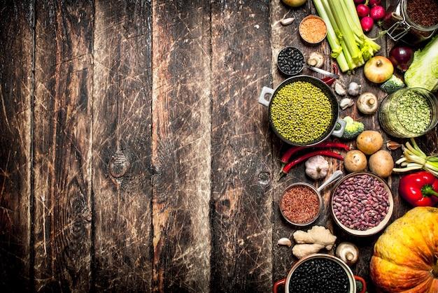 自然食品。野菜と様々な豆の種。古い木製のテーブルの上。
