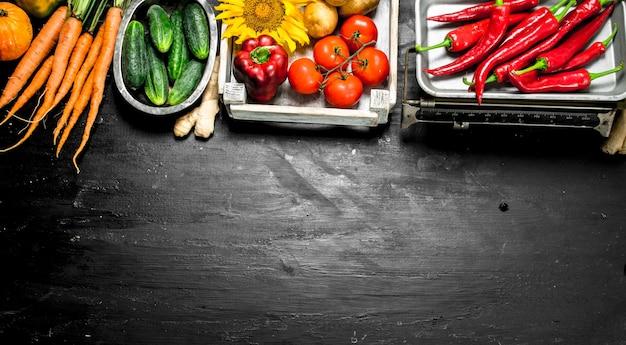 自然食品。箱に入った野菜とはかりの唐辛子。黒い黒板に。