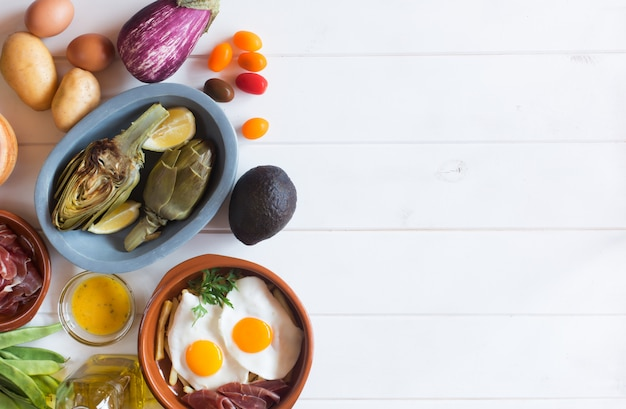 Organic food on the white table. artichokes and lemons in the plate. fried eggs and vegetables. this products people usually eat for healthy lunch