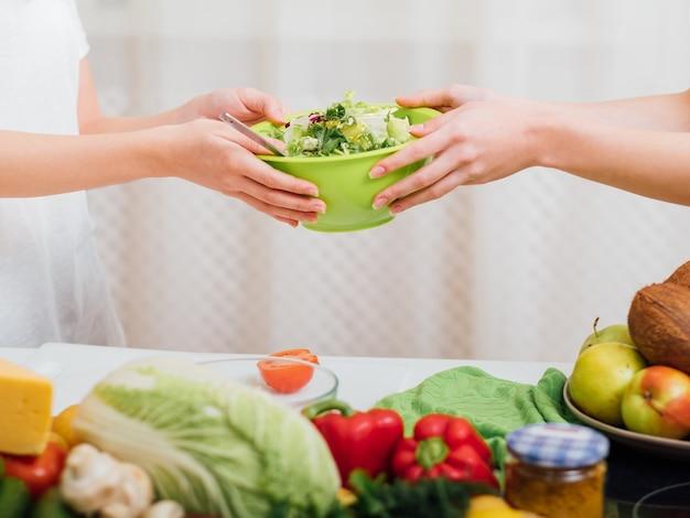 有機食品。健康的な食生活。女性の手で新鮮なサラダのボウル。周りの野菜の品揃え。