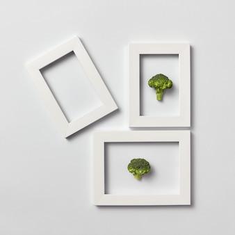 신선한 천연 브로콜리와 밝은 회색 벽에 하나의 빈 프레임이있는 유기농 프레임, 텍스트 배치. 평평하다. 채식 개념.