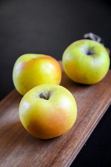 木製のまな板に有機の新鮮なリンゴ