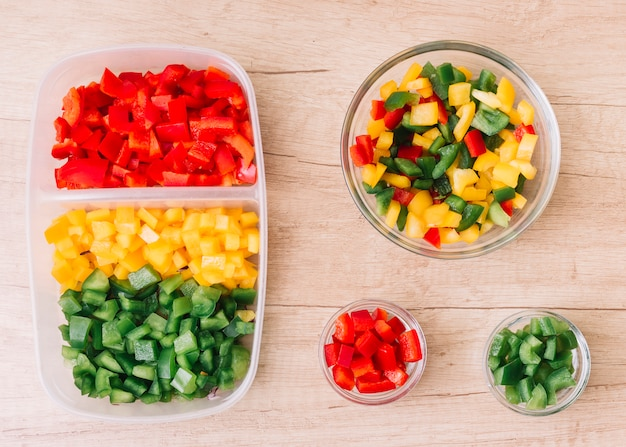 An organic fresh chopped red; green and yellow bell peppers in the tiffin box and glass bowls on wooden desk