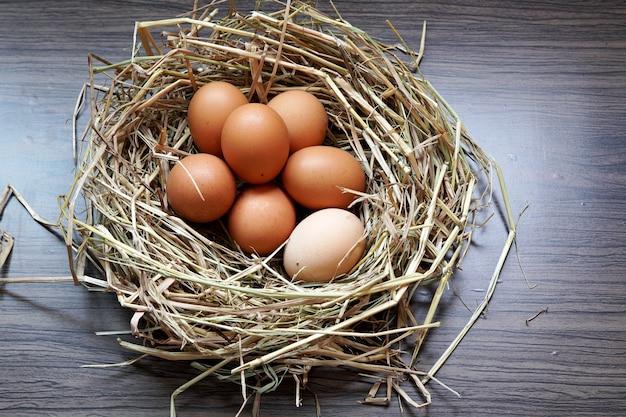 Органические свежие яйца в коричневом гнезде на деревянном столе