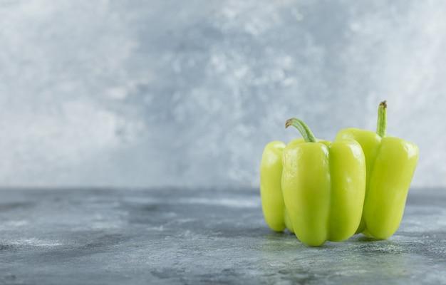 Органический свежий зеленый сладкий перец на сером фоне. фото высокого качества