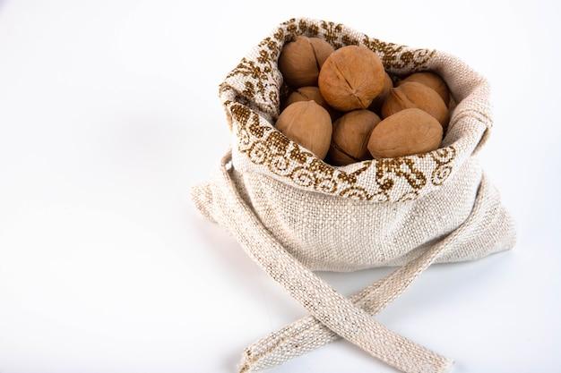 白い背景の黄麻布の袋に有機の新鮮な収穫されたクルミ Premium写真