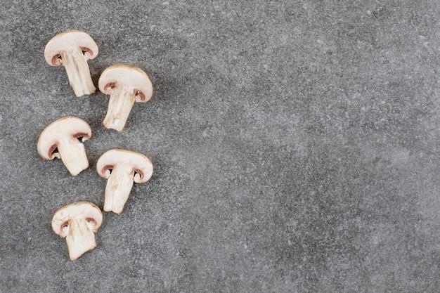 Fette di funghi freschi biologici su superficie grigia