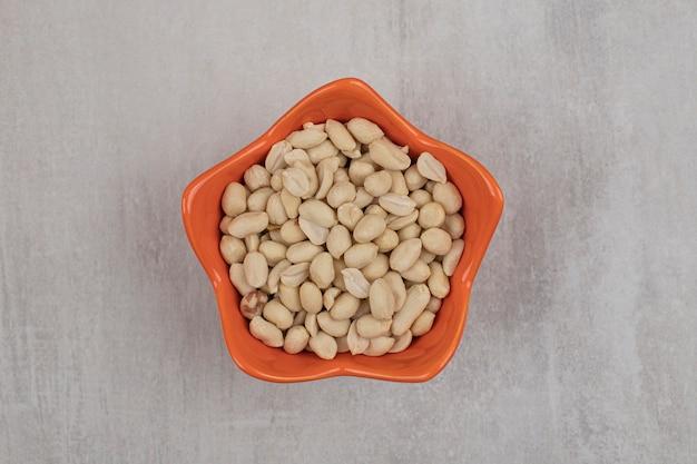Органические свежие арахисы в апельсиновой миске.
