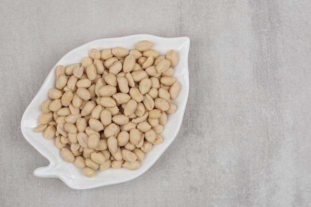 Органический свежий арахис на тарелке в форме листа.