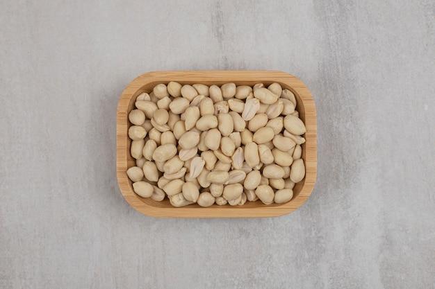 Органический свежий арахис на деревянной тарелке.