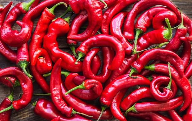 Органические свежие красные горячие перцы chili на деревенском деревянном фоне. вид сверху.