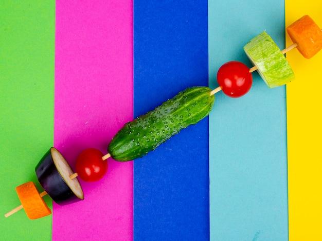 나무 막대기에 유기농 신선한 슬라이스 야채입니다. 채식주의자 또는 건강 식품 개념입니다. 색상 밝은 배경에 최소한의 정물입니다.