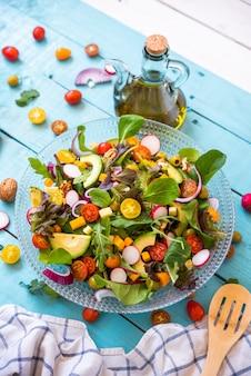 파란색 배경에 유기농 신선한 야채 샐러드와 엑스트라 버진 올리브 오일 한 병