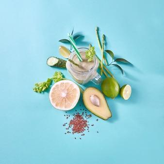 Органические свежесобранные овощи и фрукты для приготовления здорового вегетарианского коктейля в стеклянной банке на синей бумажной стене с копией пространства. плоская планировка.