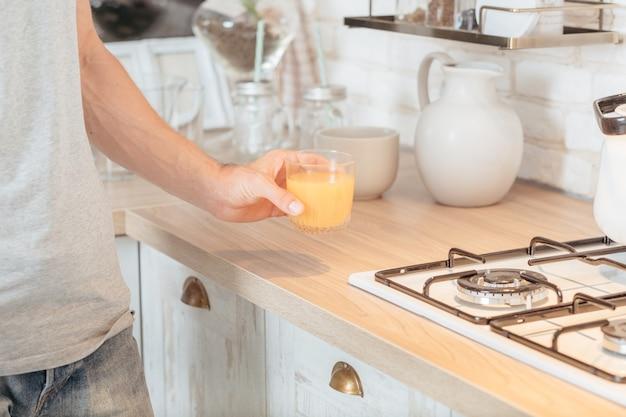 Органическое фруктовое питание. обрезанный снимок человека, принимающего стакан апельсинового сока на кухне. .