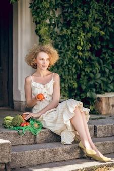 有機フルーツ。有機果物を持つ若い女性の写真