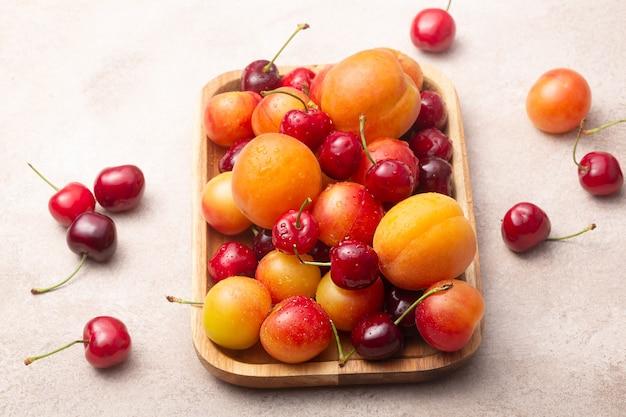 Органические фрукты и ягоды на деревянной тарелке