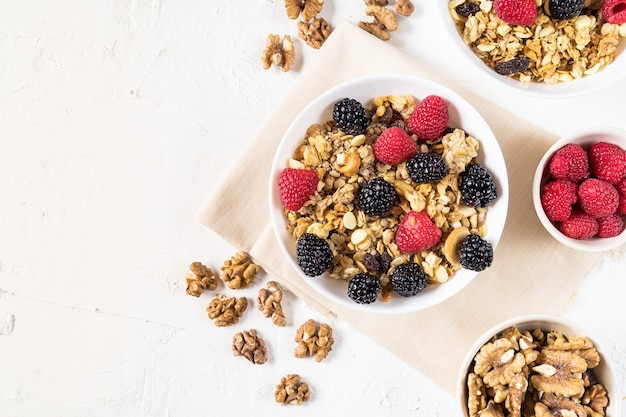 Organic granola with fresh berries and cashew nuts on white background flat lay.