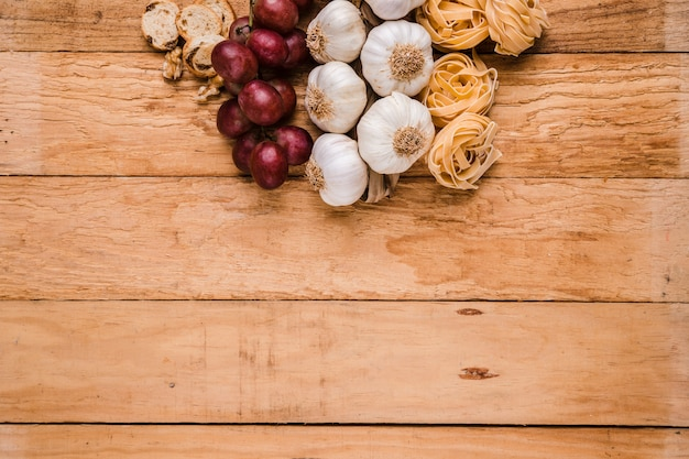 Organic grapes; bunch of garlic bulbs with raw pasta and bread over textured wallpaper
