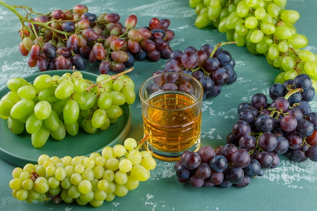 Organic grapes in a tray with drink high angle view on a plaster background