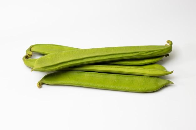 Связка органических зеленых бобов на белом изолированные