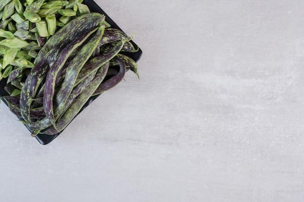黒皿に有機インゲン。高品質の写真