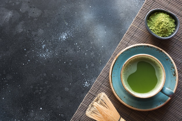 Organic green matcha tea on black table.