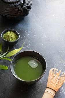 Organic green matcha tea in bowl on black table. space for text.