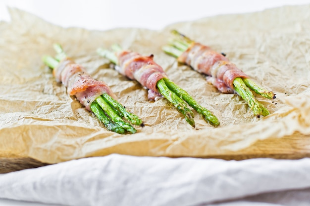 Organic green mini asparagus wrapped in bacon on wooden cutting board.