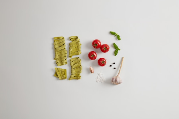 Organic green noodles with spinach, sea salt, fresh red tomatoes, garlic and basil leaves on white background. preparing nourishing dish full of carbohydrates. gluten free gourmet fettuccine