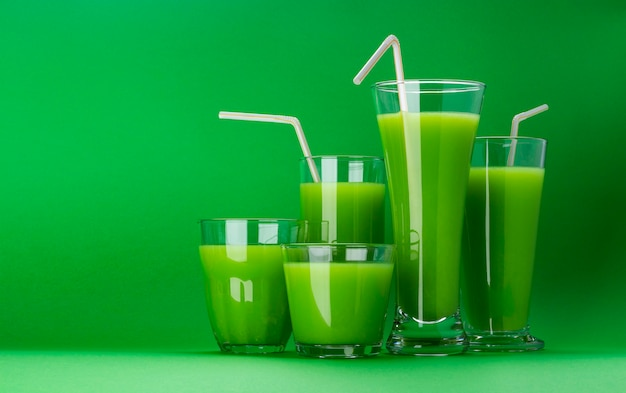 Organic green smoothie, apple juice on isolated on green background with copy space, fresh celery cocktail