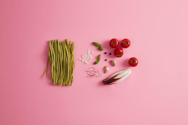 Trenette biologiche di spinaci verdi con ingredienti, spezie per preparare gustosi piatti della cucina italiana. raccolta di cibi crudi. pomodori, aglio, fili di peperoncino, insalata di cicoria, sale marino possono essere aggiunti al vostro piatto