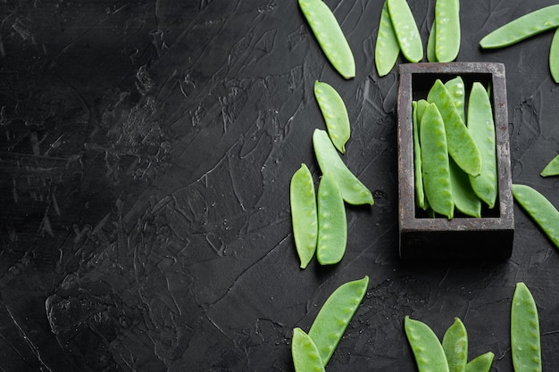 Organic green sugar snap peas ready to eat set, in wooden box, on black stone table