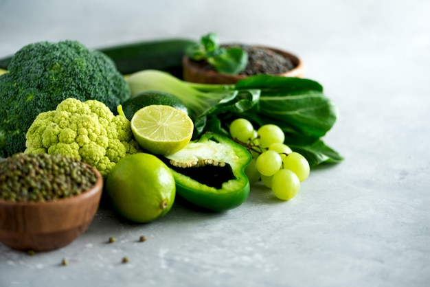Органические зеленые овощи и фрукты на сером фоне.