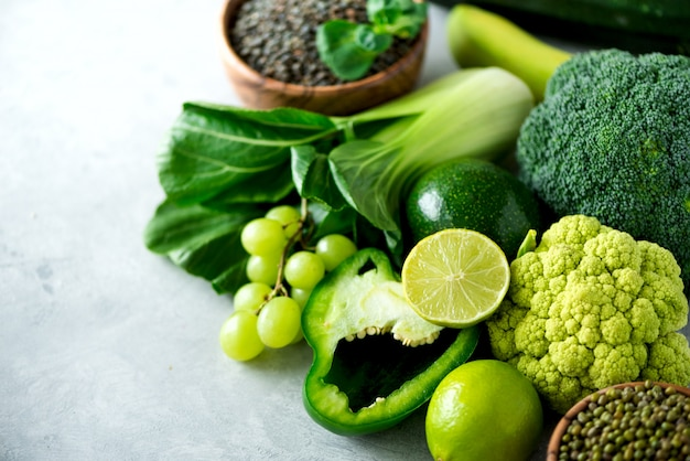 Organic green vegetables and fruits on grey background.