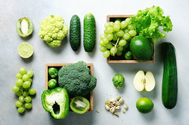 Organic green vegetables and fruits on grey. copy space, flat lay, top view. green apple, lettuce, zucchini, cucumber, avocado, kale, lime, kiwi, grapes, banana, broccoli
