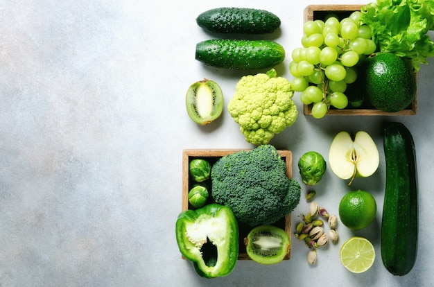 Organic green vegetables and fruits on grey . green apple, lettuce, zucchini, cucumber, avocado, kale, lime, kiwi, grapes, banana, broccoli