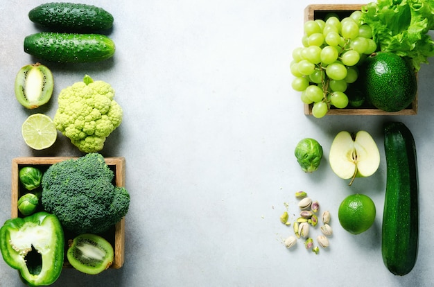 Organic green vegetables and fruits on grey .