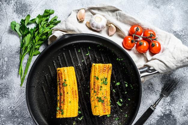 Органическая жареная кукуруза на сковороде. органические фермерские овощи. серая стена. вид сверху