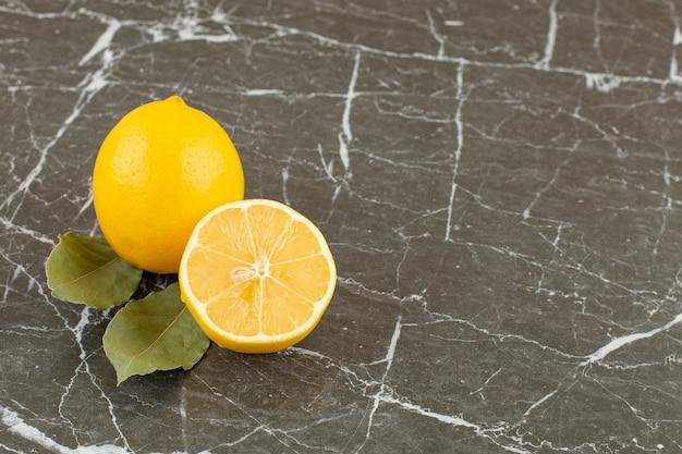 Organic half cut and whole lemons on grey stone.