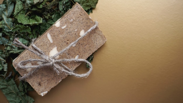 フィールドハーブで作られたオーガニックの手作り石鹸。金色の背景に乾いた草とロープで石鹸
