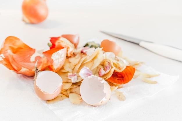 堆肥にする準備ができている有機家庭料理食品廃棄物。生態学的概念。食べ物の残り物、台所のテーブルの上の野菜の皮。環境に配慮した行動、廃棄物管理、ごみのリサイクル。