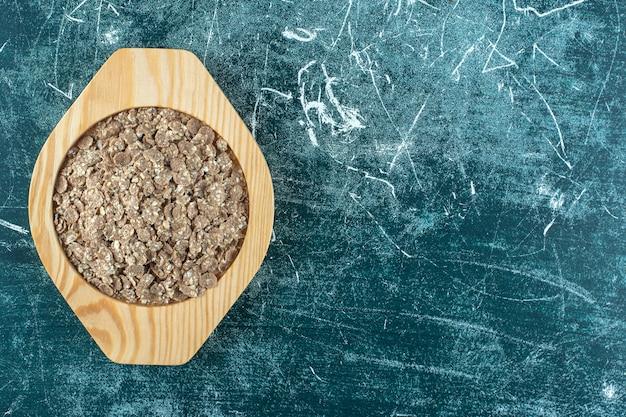 Muesli organici e fatti in casa in un piatto di legno, sullo sfondo blu. foto di alta qualità